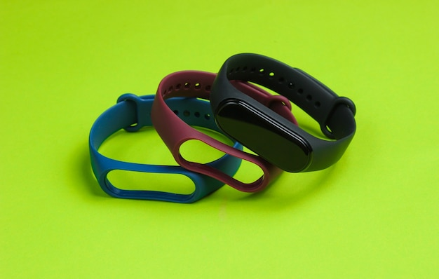 Relógio inteligente com pulseiras intercambiáveis em fundo verde. rastreador de fitness. gadgets modernos