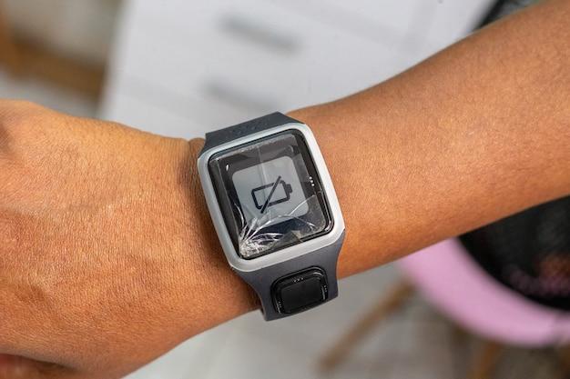 Relógio inteligente com sinal de bateria descarregada no braço de uma pessoa de cabelo preto.