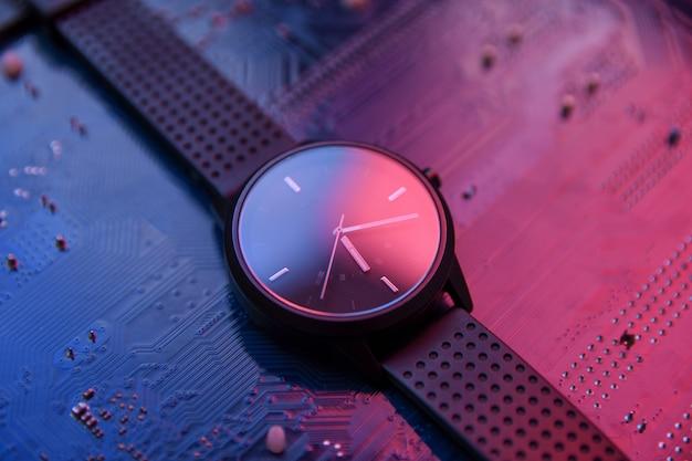 Relógio inteligente com visor analógico e uma pulseira preta na placa-mãe do computador hitec hi tec. com 2 luzes de cor vermelha e azul.