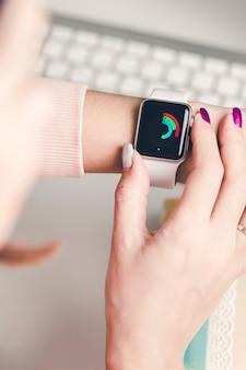 Relógio inteligente inteligente para uma mão feminina em uma luz