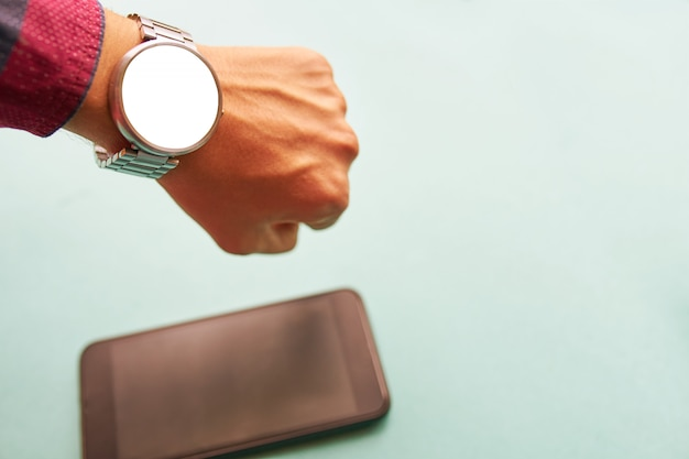 Relógio inteligente na mão com tela isolada, em branco para maquete e smartphone na mesa na