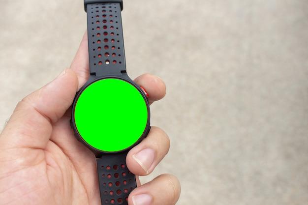 Relógio inteligente na mão com tela verde em branco para mock-up