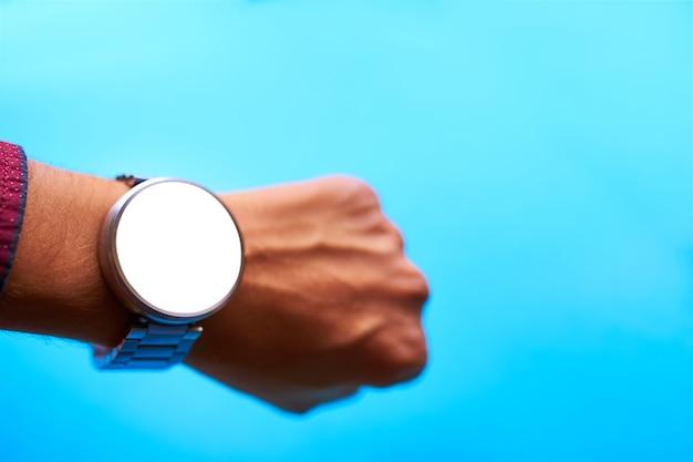 Relógio inteligente na mão no fundo azul