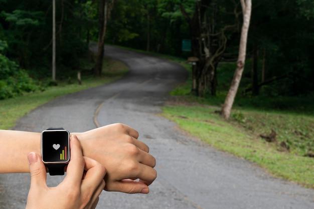 Relógio inteligente na mão para verificação de saúde, corrida em trilha