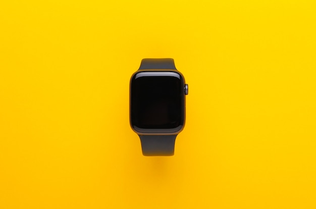 Relógio inteligente preto sobre fundo amarelo.