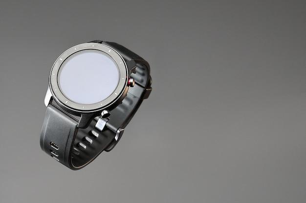 Relógio inteligente sem fio em uma caixa redonda preta fosca com riscos no aro e uma pulseira de silicone em um fundo cinza com espaço para texto.