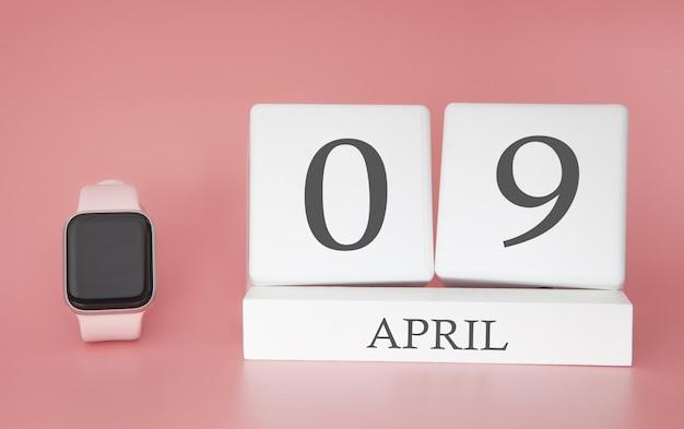 Relógio moderno com calendário de cubo e data 09 de abril em fundo rosa. férias de primavera conceito.
