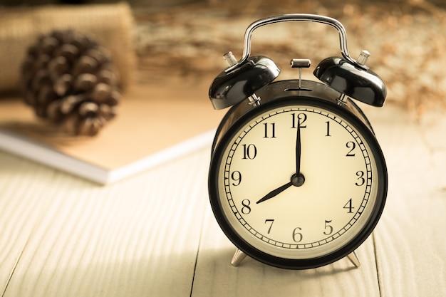 Relógio mostra o horário oito horas, relógio em uma mesa de madeira com luz natural