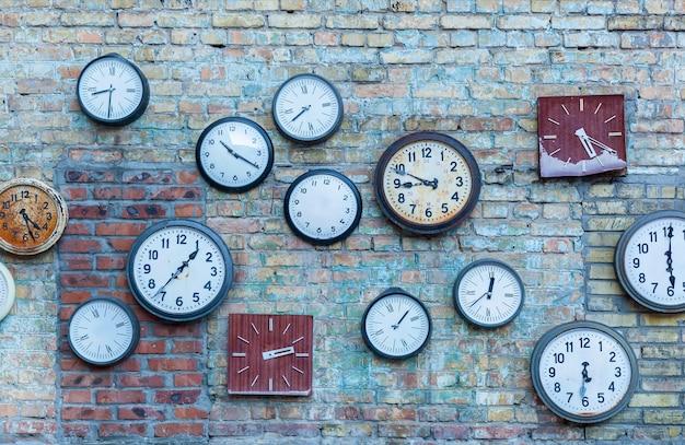 Relógio múltiplo. pluralidade dos diferentes relógios na velha parede de tijolos.