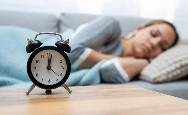 Relógio na frente da mulher dormindo