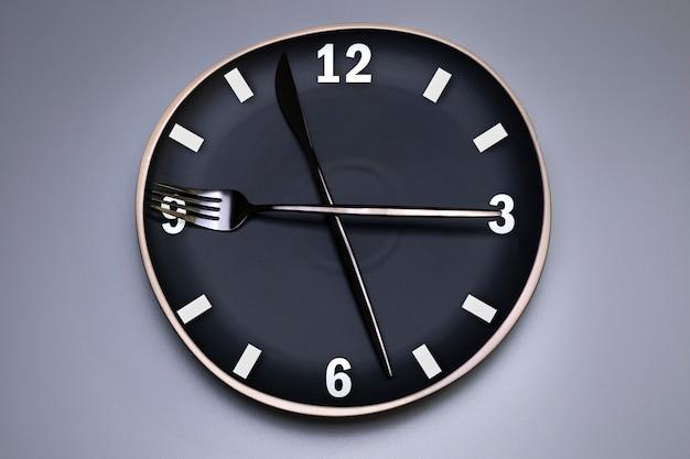 Relógio na placa preta, com talheres, fundo cinza. o conceito de jejum intermitente, hora do almoço, dieta e perda de peso. é hora de fazer dieta.