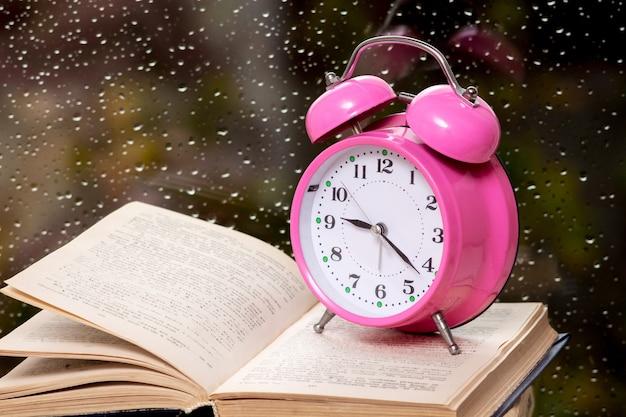 Relógio no livro desdobrado perto da janela com gotas de chuva