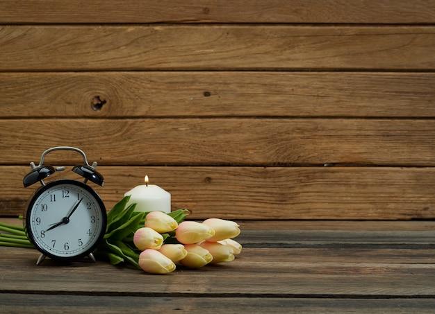 Relógio preto e tulipa na mesa.