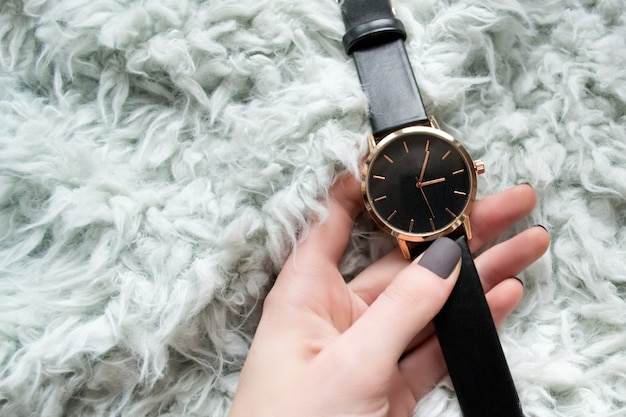 Relógio preto elegante em uma mão feminina