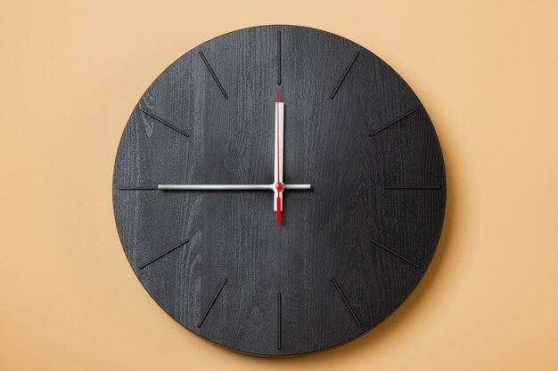 Relógio preto marca nove horas em fundo bege claro