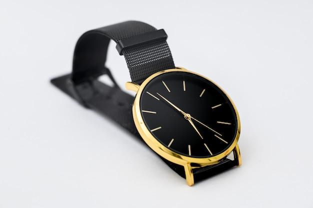 Relógio preto para homens na parede branca.
