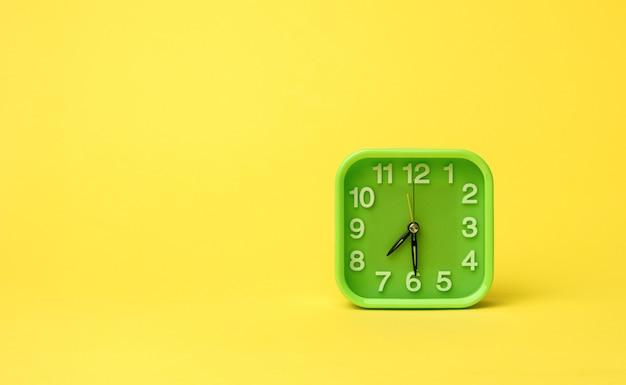 Relógio quadrado verde com números brancos em uma parede amarela, copie o espaço