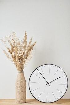 Relógio redondo clássico e vaso caseiro com planta seca na mesa de madeira