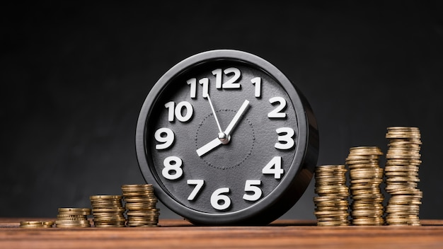 Relógio redondo entre as moedas crescentes na mesa de madeira contra o pano de fundo preto