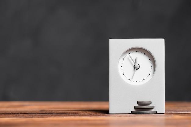 Relógio retangular moderno na mesa de madeira texturizada contra fundo preto