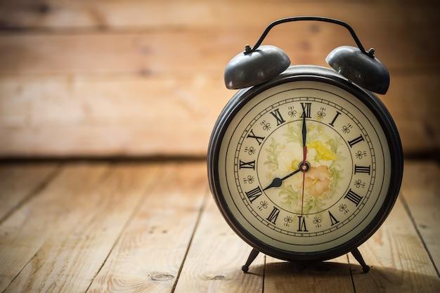 Relógio retrô com número antigo está mostrando 08:00 em fundo de madeira