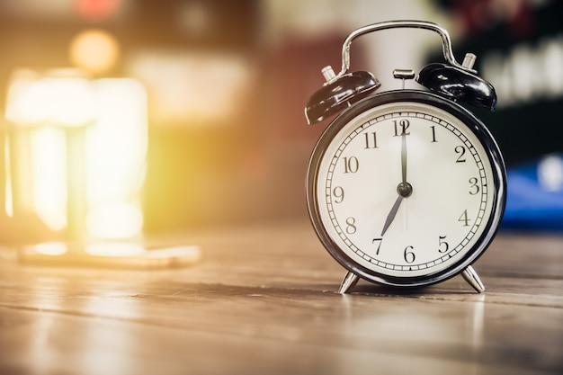 Relógio retro de 7 horas na mesa de madeira com fundo de luz do sol