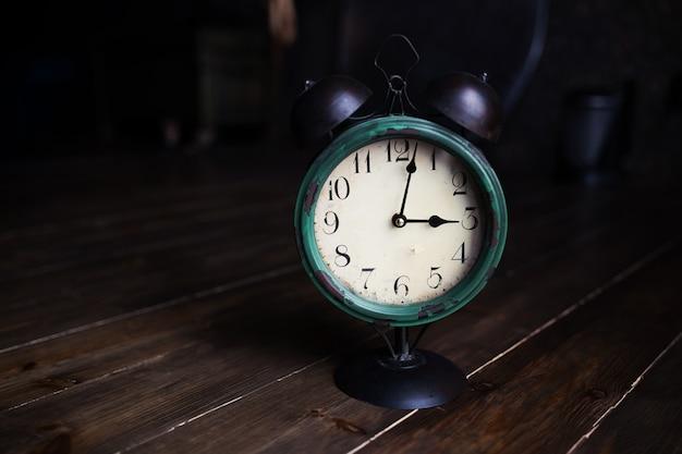 Relógio retrô em um velho piso de madeira.