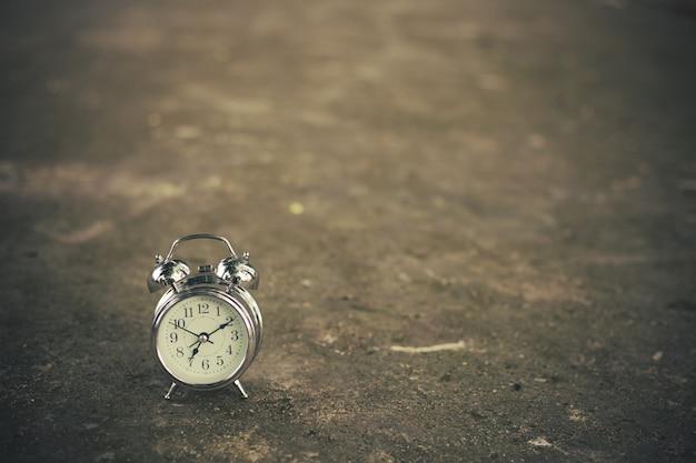 Relógio retrô no chão de tijolos