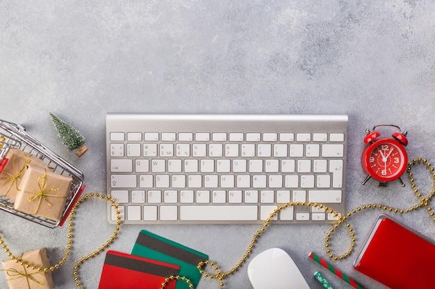 Relógio vermelho, caderno azul, teclado, presentes na cesta, cartões de crédito em cinza