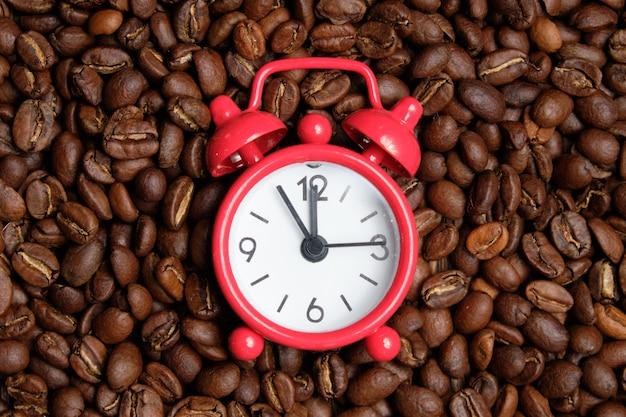 Relógio vermelho de grãos de café. conceito o tempo necessário para fritar.