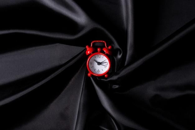 Relógio vermelho em tecido preto. hora de fazer compras.