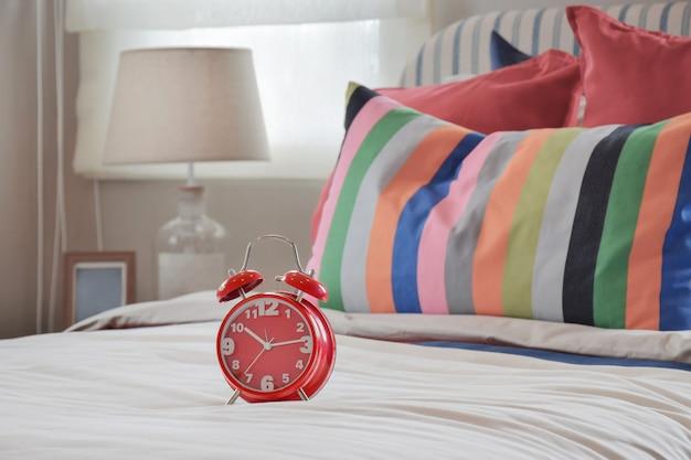 Relógio vermelho no manto branco e almofadas listradas coloridas