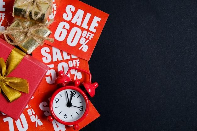 Relógio vintage com caixas de presente em adesivos vermelhos com descontos