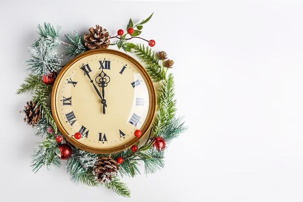 Relógio vintage com decoração de natal em parede branca, meio-dia, véspera de ano novo