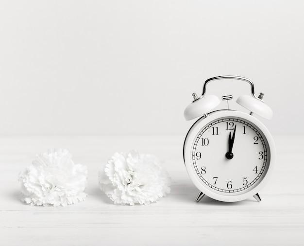 Relógio vintage com flores brancas ao lado