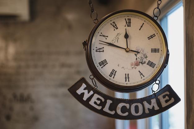 Relógio vintage com número romano e etiqueta de boas-vindas pendurado