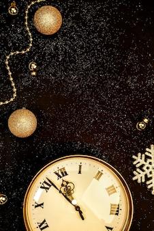 Relógio vintage dourado decorado com bolas de natal em um fundo preto com brilhos