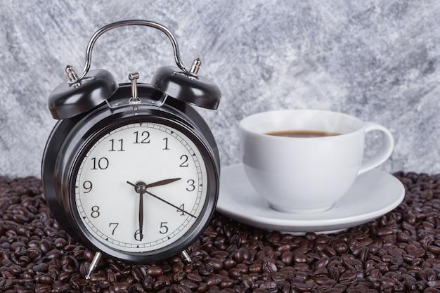 Relógio vintage e café na xícara (conceito de hora do café) com fundo de parede
