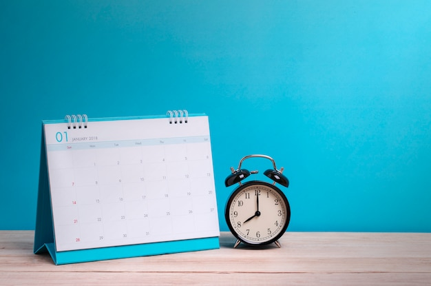 Relógio vintage e calendário na madeira, conceito de tempo