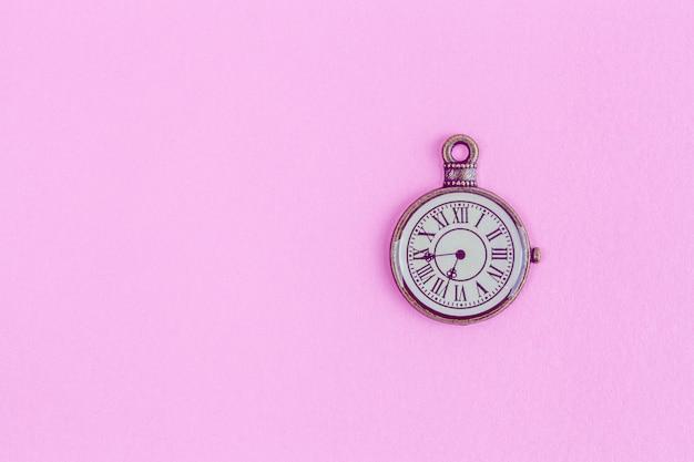 Relógio vintage em bronze no fundo rosa - vista superior com espaço de texto