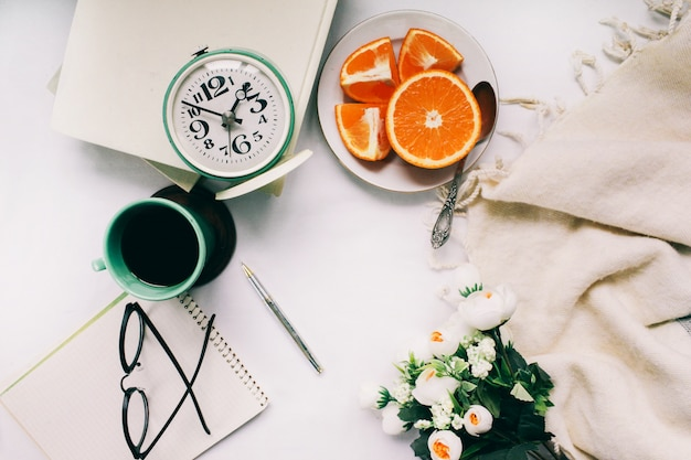 Relógio vintage em uma mesa com uma xícara de café quente e frutas frescas