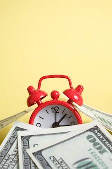 Relógio vintage vermelho com muitos cem notas de dólar dos eua em amarelo