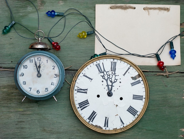 Relógios antigos e bloco de notas artesanal na superfície de madeira verde