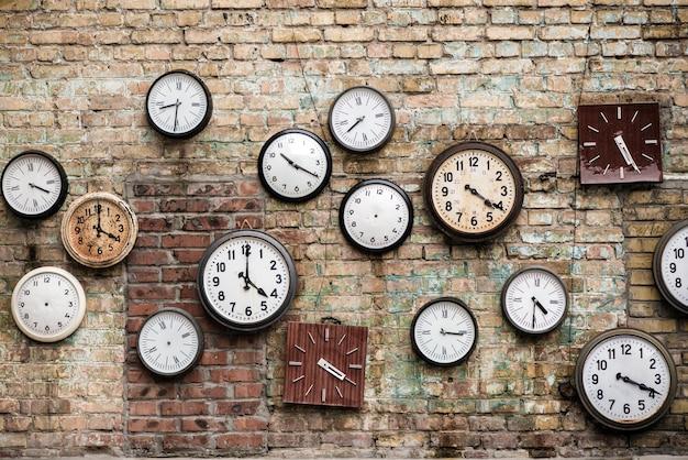 2c39a33d813 Relógios antigos localizados na parede de tijolos