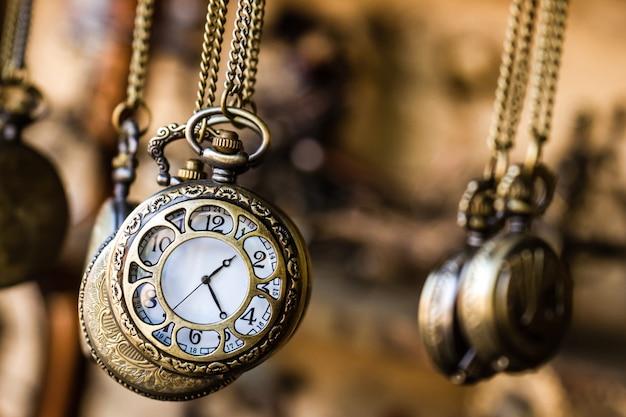 Relógios de bolso vintage pendurados com correntes em uma loja de antiguidades
