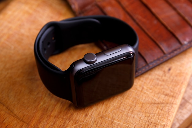 Relógios espertos pretos luxuosos na madeira.