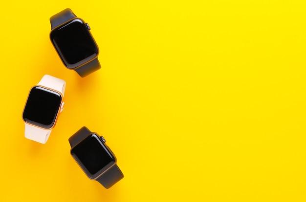 Relógios inteligentes preto e rosa sobre fundo amarelo.