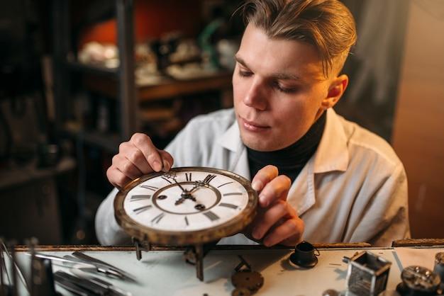 Relojoeiro ajusta o mecanismo de relógios antigos