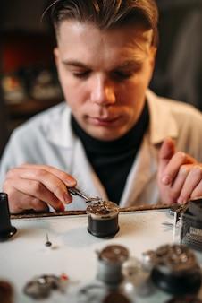 Relojoeiro conserta um relógio quebrado com uma pinça