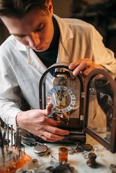 Relojoeiro segurando um relógio de mesa antigo